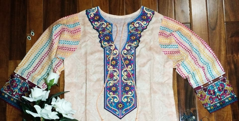 Colorful top with embroidered neck line. Beautiful tussles at the bottom line